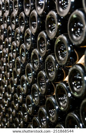 Dark cellar with old bottles of wine. - stock photo