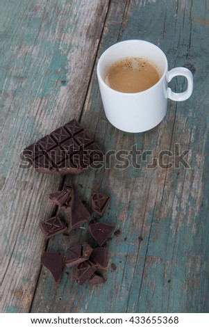 Dark chocolate and a cup of coffee on old, vintage table, stock photo - stock photo
