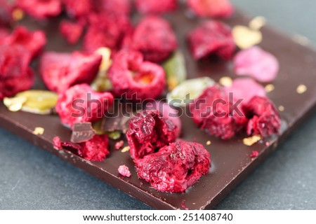 Dark  chocolate bar with berry fruits, rose petals, pistachios and gold powder - stock photo