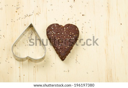 Dark chocolate chia seed love heart cookie and cookie cutter on wooden background - stock photo