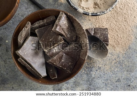 dark chocolate chunks in wooden bowl, on oak table - stock photo