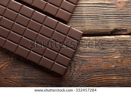 Dark chocolate on old wood background - stock photo