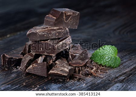 Dark chocolate pieces, cocoa powder and cocoa beans on a wooden table - stock photo