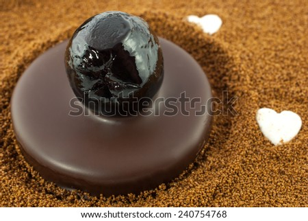 Dark chocolate praline with candied cherry on barley coffee background - stock photo