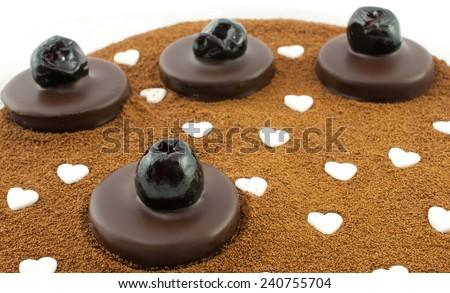 Dark chocolate pralines with candied cherries on barley coffee background - stock photo