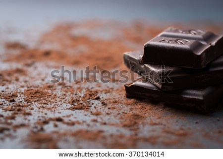 Dark chocolate stack with cocoa powder on a stone background with copy space, selective focus