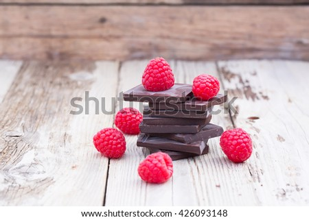 Dark chocolate stack with fresh raspberries, on wooden table. Natural light, selective focus. - stock photo