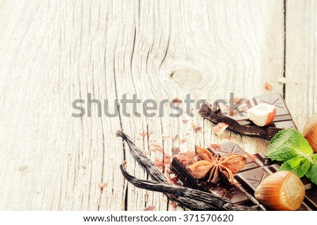 Dark chocolate tablet with vanilla and hazelnuts on old wooden background  - stock photo