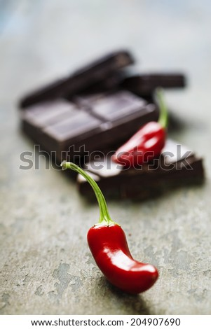 Dark chocolate with chili pepper over wooden background - stock photo