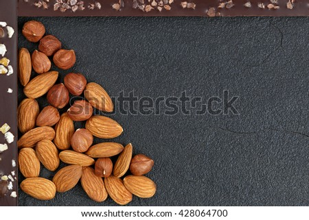 Dark chocolate with coffee beans, fruit and with almonds on dark stone background. Prepared for the World Chocolate Day. Photographed macro - stock photo