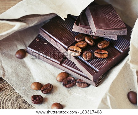 Dark chocolate with coffee beans on textured paper background - stock photo