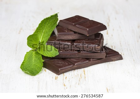 Dark chocolate  with fresh mint on a white background wooden, selective focus