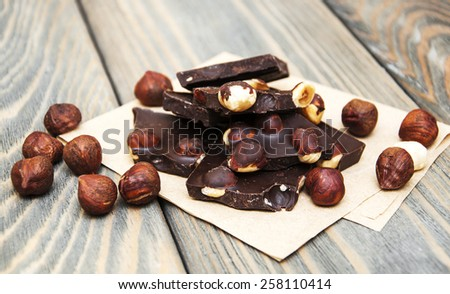 Dark  chocolate with nuts on a wooden background - stock photo