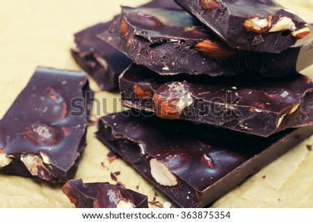 Dark chocolate with nuts on  on crumpled paper. Stack of assorted dark chocolate. - stock photo