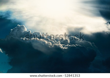 Dark cloud on sky with sun light beams - stock photo