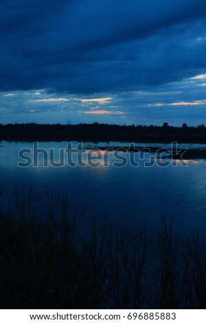 Dark clouds at sunset over the lake trees in Silhouette