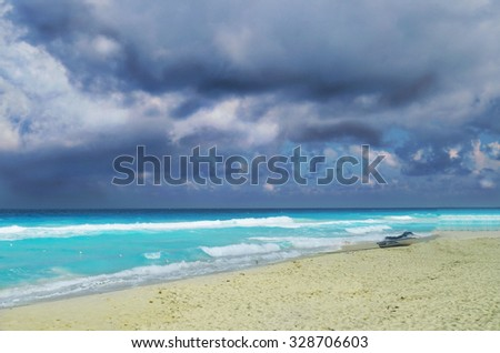Dark clouds over blue sea and near the white sand