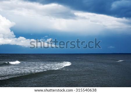 Dark clouds over dark Baltic sea. - stock photo