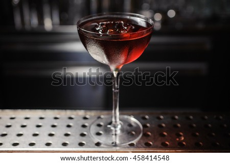 dark cocktail on a  bar setting - stock photo