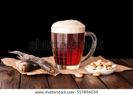 dark cold beer in a frosty mug on dark wooden table. dry fish, pistachios on paper