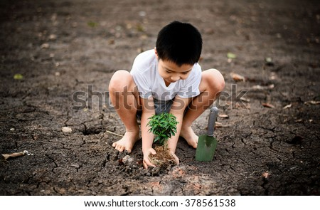 Dark color tone, Young Thai boy planting little seedling on dry and crack empty land. Earth day concept. - stock photo
