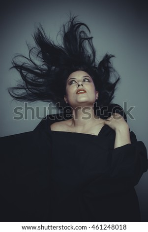 Dark concept, Brunette woman in studio shot with wind on hair .