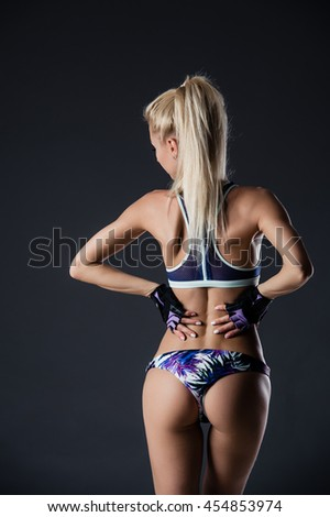 Dark contrast image of fitness woman's back and buttocks. She is training on black background in studio.