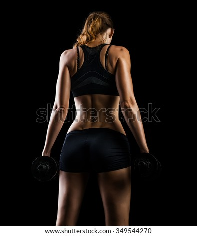 Dark contrast photo of back side of young beautiful fitness woman with beads of sweat which training in gym. Working out with dumbbells on black background