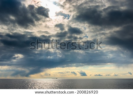 dark cumulus clouds hovering over the sea - stock photo