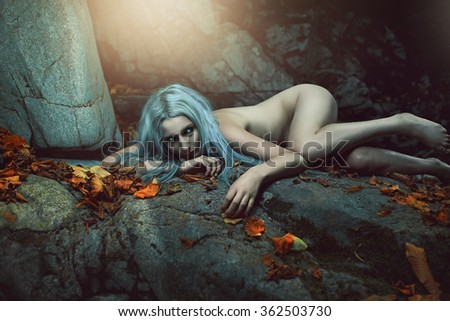 Dark daughter of the forest resting on rocks. Fantasy and myth   - stock photo
