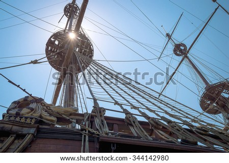 Dark detail of an old wooden pirate's ship in a shade with the sun shining through the mast, with ropes and other equipment in the shade. Artistic angle crop and dark shade. - stock photo