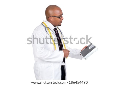 Dark doctor posing with weight scale and measuring tape