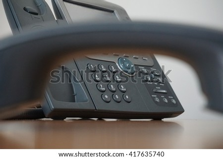 Dark earphone (receiver) with a corporate business landline telephone in the background