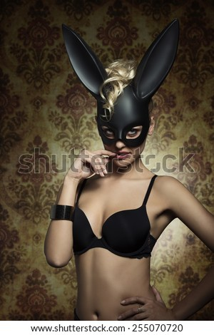 Dark easter portrait of erotic blonde woman in sexy lingerie posing with bizarre bondage dark bunny mask. Looking in camera with charming eyes  - stock photo