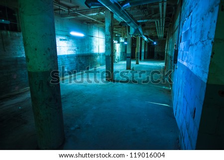 Dark empty older warehouse / commercial space lit in blue - stock photo