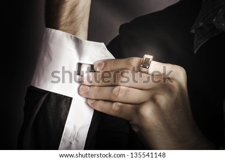 Dark fashion photograph of a stylish man putting cuff links on his white colored shirt