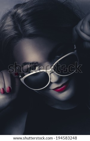 Dark fashion portrait on the face of an elegant female model in sunglasses with red lips makeup and matching nails. Styling in the shadows - stock photo