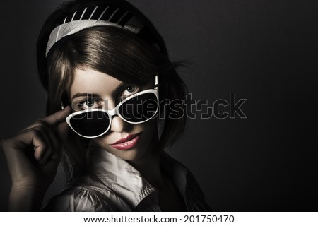 Dark fashion portrait on the head of a beautiful fashion girl wearing retro pinup sunglasses on face with attractive short brunette hair style and pretty makeup. Face of dark retro fashion - stock photo