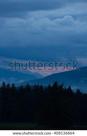 dark forest in front of a mountain chain with ascending mist, cloudy sky after sunset with reddish shining horizon
