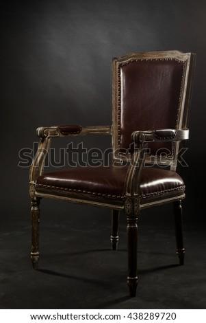 Dark genuine leather vintage chair. Old vintage furniture. - stock photo