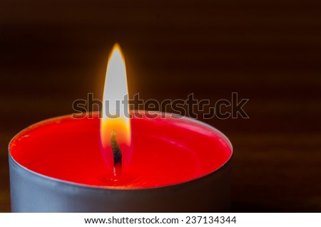 Dark glowing red tea light on wooden table - stock photo
