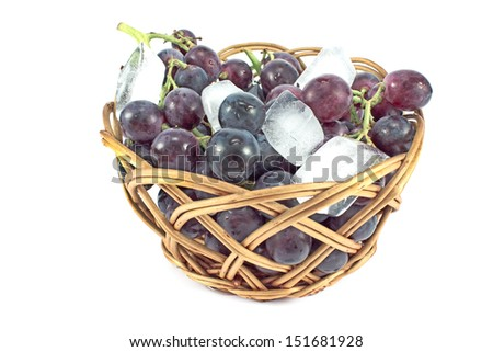 Dark grapes in a basket with ice isolated on white - stock photo