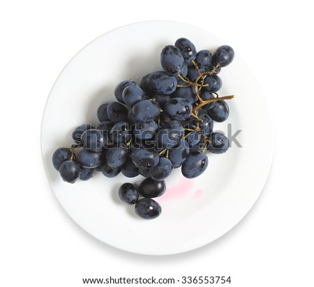 Dark grapes in plate on a white background - stock photo