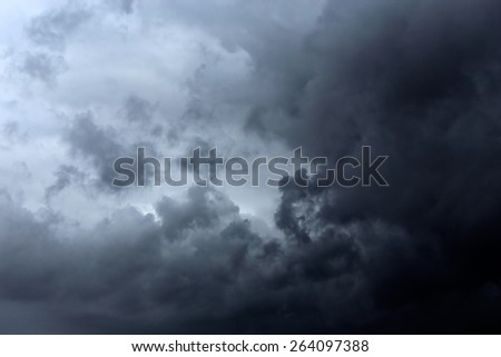 Dark gray and black clouds with some interesting light - stock photo