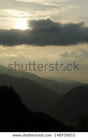 Dark gray storm clouds above layers of misty mountains.
