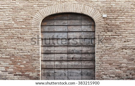 Dark gray wooden door with arch in old brick wall, background photo texture - stock photo