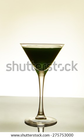 dark-green cocktail on a light background