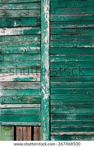 dark green wall from wooden planks with cracked paint. - stock photo