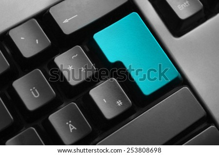 dark grey keyboard teal colored enter button - stock photo