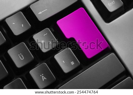 dark grey keyboard with purple colored enter button - stock photo